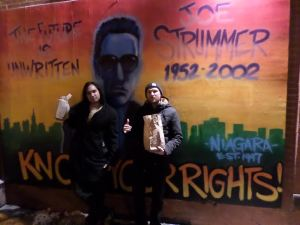 In front of the old Joe Strummer mural on East 7th. Too old for 40s- we're baggin' cheese fries and fried oreos.